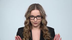 Businesswoman is reporting and tells a lot of interesting news against grey background, slow motion. Businesswoman is reporting and tells a lot of interesting stock video footage