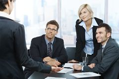 Businesswoman reporting to colleagues. Colleagues listening to businesswoman's report in meeting room in office stock photography