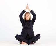 Businesswoman resting on floor doing yoga Stock Images