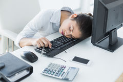 Businesswoman resting head on keyboard in office Royalty Free Stock Image