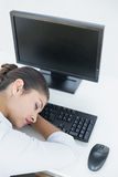 Businesswoman resting head on keyboard in office Stock Photo