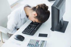 Businesswoman resting head on keyboard in office Stock Photography