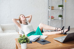 Businesswoman resting relaxing legs on the table hands behind her head and sitting  a chair in office. Stock Images