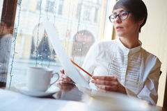 Businesswoman Reviewing Contracts in Cafe Stock Images