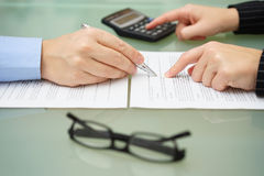 Businesswoman is reviewing document with tax consultant and making calculations to optimize report.  stock image
