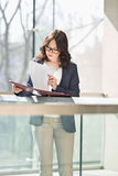 Businesswoman reviewing documents against railing in office Stock Photo