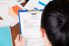 Businesswoman reviewing resume. Young businesswoman or recruiter reviewing resume for opening position, sitting at the desk with laptop and documents in office Royalty Free Stock Images