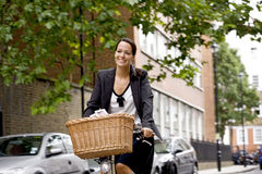 A businesswoman riding a bicycle, smiling Royalty Free Stock Images