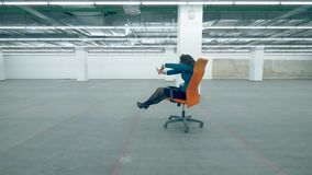 Businesswoman riding a chair, having fun at the office. 4K stock footage