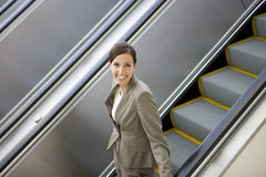 Businesswoman riding on escalator Royalty Free Stock Images