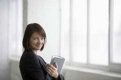 Businesswoman With Ring Binder Smiling In Warehouse Royalty Free Stock Photos