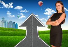Businesswoman with road climbs up Stock Photo