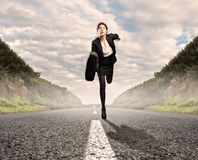 Businesswoman on a road running Stock Photography