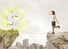 Businesswoman on rock mountain with a dollar mark Royalty Free Stock Photography