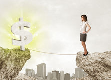 Businesswoman on rock mountain with a dollar mark Royalty Free Stock Image