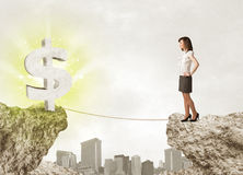 Businesswoman on rock mountain with a dollar mark Royalty Free Stock Photo
