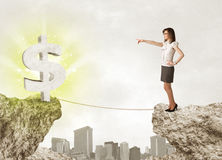 Businesswoman on rock mountain with a dollar mark Stock Photo