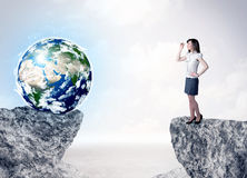 Businesswoman on rock mountain with a globe Stock Photos