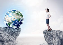 Businesswoman on rock mountain with a globe Stock Image