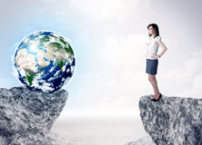 Businesswoman on rock mountain with a globe Royalty Free Stock Photos
