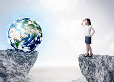 Businesswoman on rock mountain with a globe Stock Images
