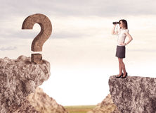 Businesswoman on rock mountain with a question mark Stock Image