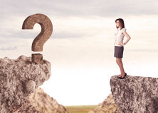 Businesswoman on rock mountain with a question mark Stock Images