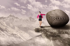 Businesswoman and rock of success outdoor Stock Photos