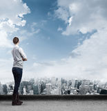 Businesswoman on roof looking at city Stock Image