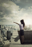 Businesswoman on roof pointing at sky Royalty Free Stock Photo
