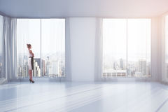 Businesswoman in room. Businesswoman standing in empty interior with curtains and windows with New York city view. 3D Rendering Stock Photos