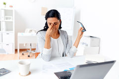 Businesswoman rubbing tired eyes at office. Business, overwork, deadline, vision and people concept - tired businesswoman with glasses working at office and Stock Images