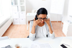 Businesswoman rubbing tired eyes at office. Business, overwork, deadline, vision and people concept - tired businesswoman with glasses working at office and Royalty Free Stock Image