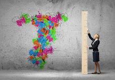 Businesswoman with ruler. Young businesswoman measuring question mark with big ruler Stock Photos