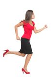 Businesswoman running. Isolated. Cutout of beautiful business woman casual dressed in red running in high heels in profile in full length. Isolated on white Royalty Free Stock Photography