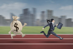 Businesswoman running with a bag of dollar Stock Image