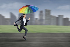 Businesswoman running with colorful umbrella Royalty Free Stock Image
