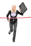 Businesswoman running and reaching the finish line Stock Photos