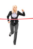 Businesswoman running and reaching the finish line Royalty Free Stock Photography