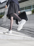 Businesswoman In Running Shoes Walking Up Steps Royalty Free Stock Image