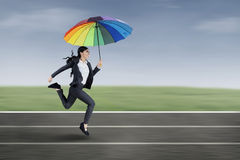 Businesswoman running under an umbrella Stock Image