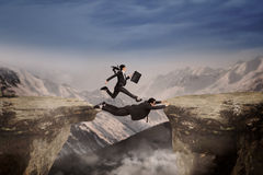 Businesswoman runs through her partner. Concept of cooperation in business team. Woman runs above her partner for past the gap Stock Image