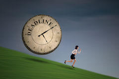 Businesswoman runs out of deadline on a hill Stock Images