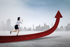 Businesswoman runs on the upward arrow Stock Image