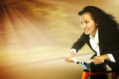 Businesswoman In A Rush Riding A Bicycle To Work. Businesswoman in a rush riding a bicycle in a sunny day showing motion movement to reach a goal Royalty Free Stock Photo