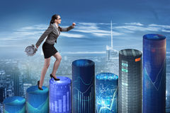 The businesswoman rushing with clock on bar charts Royalty Free Stock Photography