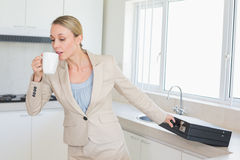 Businesswoman rushing out the door to work in the morning. At home in the kitchen stock photo