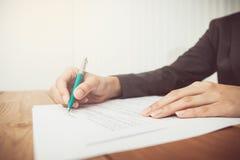 Businesswoman& x27; s-hand med pennan som avslutar personlig information arkivfoto