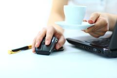 Businesswoman's hand on mouse and cup of coffee Royalty Free Stock Photos