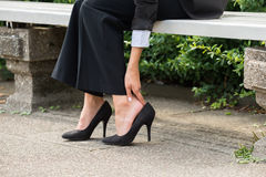 Businesswoman`s Hand Removing High Heels. Close-up Of Businesswoman`s Hand Sitting On Bench Removing High Heels Royalty Free Stock Photos